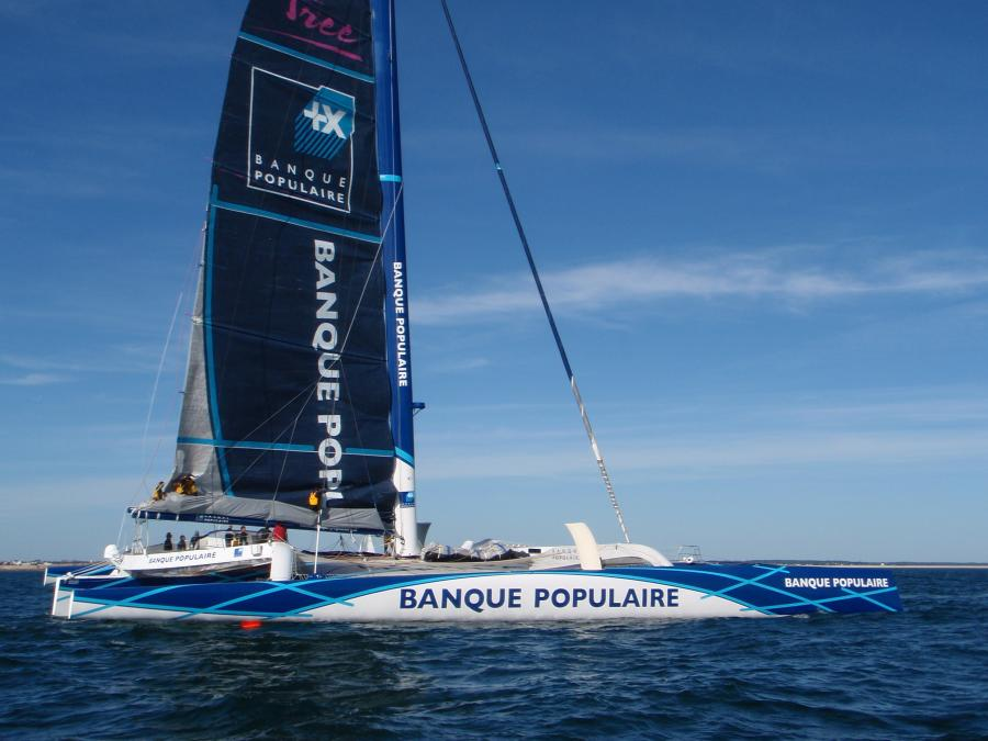 Banque Populaire having much trouble in getting its mainsail down. Note crowd on boom.